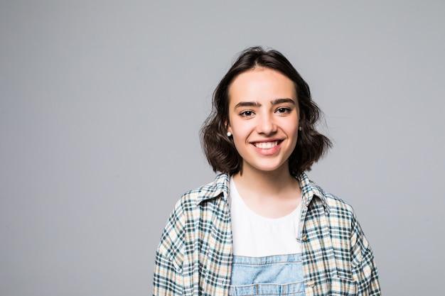 歯を浮かべて、探しているカジュアルな灰色のシャツに黒い長い髪を持つ陽気な美しい少女の肖像画を閉じる 無料写真
