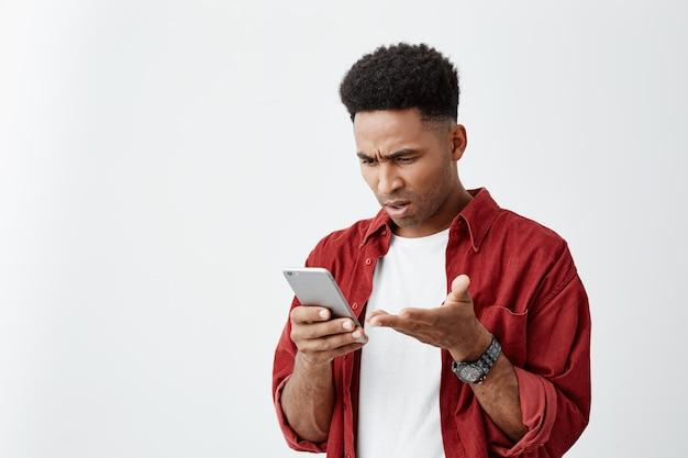 ガールフレンドと主張して混乱した表情で携帯電話を見て赤いシャツとカジュアルな白いtシャツでアフロのヘアカットと若いハンサムな日焼け肌の肖像画を間近します。 無料写真