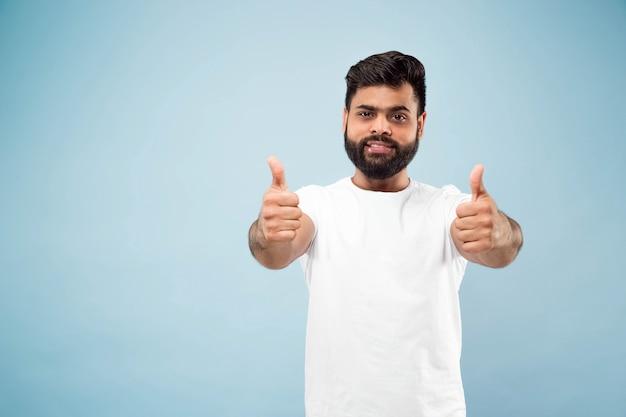 白いシャツを着た若いインド人の肖像画をクローズアップ。 ok、いい、素晴らしいのサインを示しています。笑顔。 無料写真