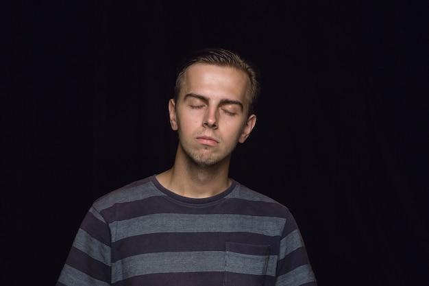孤立した若い男の肖像画をクローズアップ。目を閉じた男性モデル。思いやりがある。顔の表情、人間性、感情の概念。 無料写真