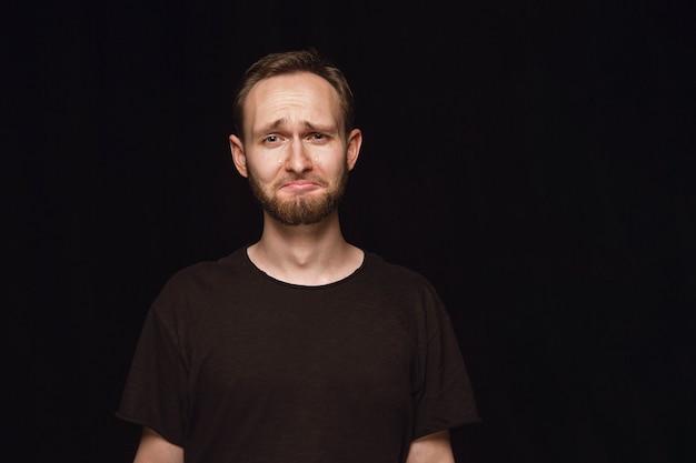 Закройте вверх по портрету молодого человека, изолированному на черном пространстве. фотоснимок настоящих эмоций мужской модели. плач, грустный, унылый и безнадежный Бесплатные Фотографии