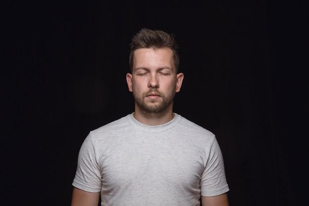 Закройте вверх по портрету изолированного молодого человека. настоящие эмоции мужской модели с закрытыми глазами. вдумчивый. выражение лица, концепция человеческой природы и эмоций. Бесплатные Фотографии