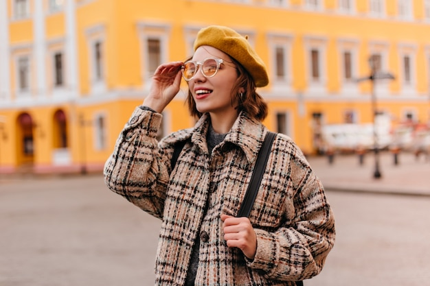 都市の景観を賞賛するサングラスの若い女性のクローズアップの肖像画 無料写真
