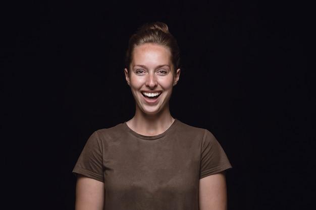 검은 스튜디오 배경에 고립 된 젊은 여자의 초상화를 닫습니다. 여성 모델의 실제 감정이 담긴 포토 샷. 웃고, 미친 행복 함을 느끼고, 웃음. 표정, 인간의 감정 개념. 무료 사진