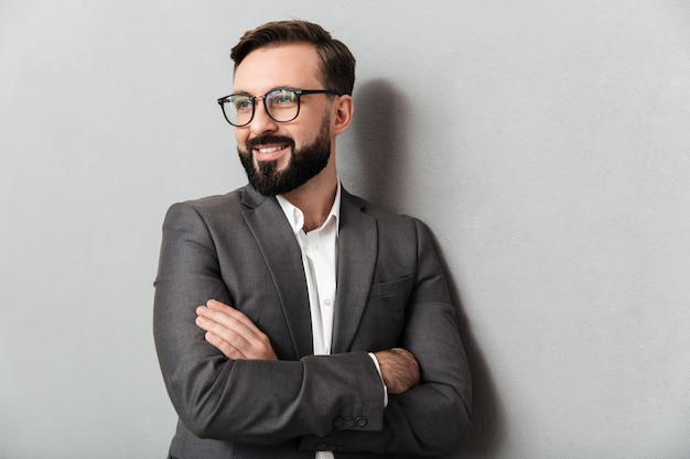 Close up ritratto di compiaciuto uomo senza barba in occhiali alla ricerca sulla fotocamera con un sorriso sincero, in piedi con le braccia conserte isolato su grigio Foto Gratuite