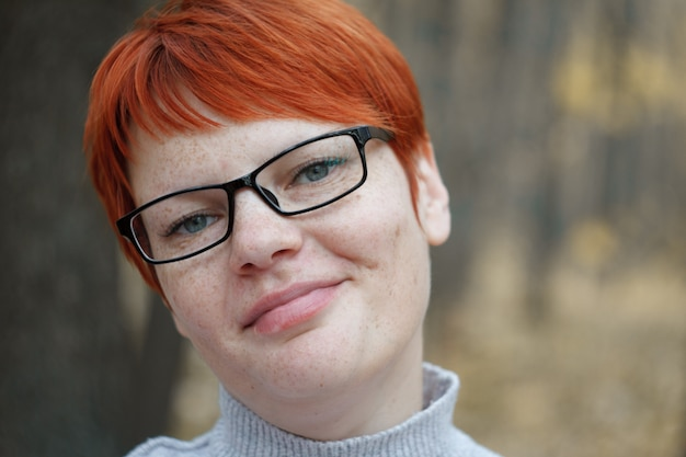 Close-up portrait of a red-haired woman with glasses Premium Photo