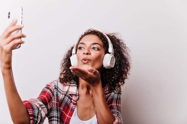 Ritratto del primo piano della donna nera romantica che invia i baci dell'aria mentre ascolta la musica. giovane signora alla moda in cuffie utilizzando smartphone per selfie. Foto Gratuite