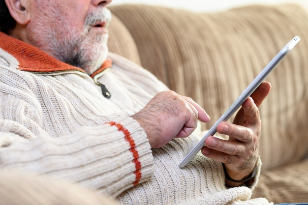 Close up portrait of senior man sitting on sofa and using digital tablet in living room. Premium Photo