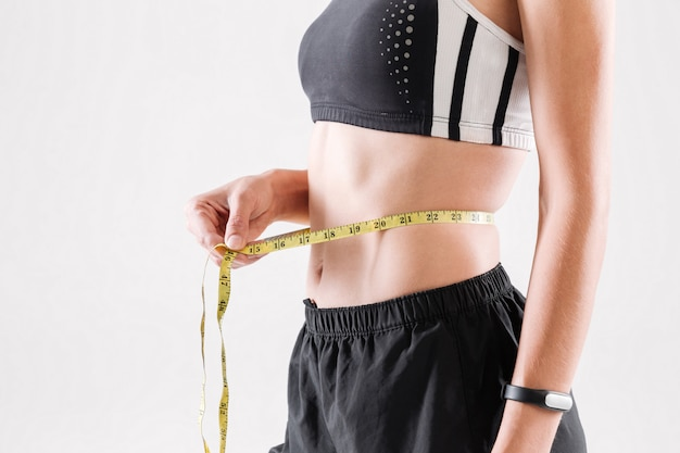 Close up portrait of a slim sportswoman measuring her waist Free Photo