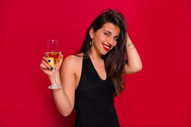 Ritratto del primo piano della donna felice sorridente con capelli scuri lunghi che posano con un bicchiere di champagne sopra fondo rosso isolato Foto Gratuite