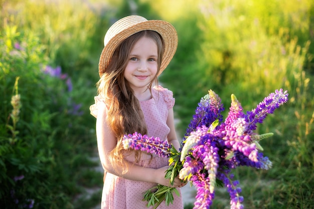 Close up portrait of a smiling little girl in a straw hat and with a large bouquet of lupins. Premium Photo