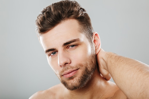 Close up portrait of a smiling man combing his hair Free Photo