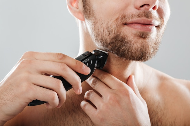 Close up portrait of a smiling man shaving his beard Free Photo