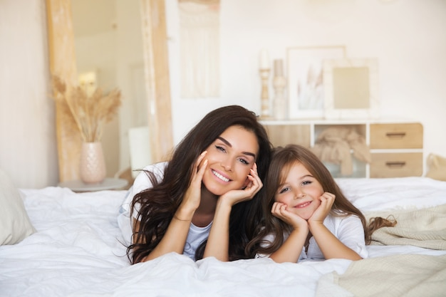 Close-up portrait of smiling mother and daughter laying in bed early in the morning in the white scandinavian Premium Photo