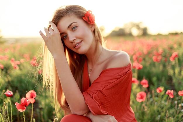 Chiuda sul ritratto di giovane donna dai capelli lunghi sorridente che cammina nel campo di papaveri la sera. caldi colori del tramonto. Foto Gratuite