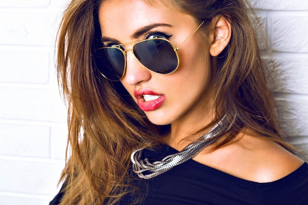 Chiuda sul ritratto di splendida donna bruna sexy, gioielli di lusso, occhiali da sole vintage, stile urbano. trucco luminoso dei capelli lunghi. Foto Gratuite