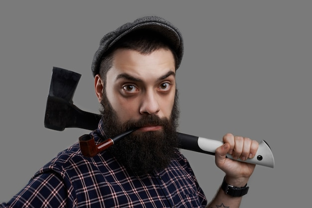 Close up portrait of surprised beard man smoking pipe and hold axe in tattooed hand. strong and serious male portrait isolated on grey background. Free Photo