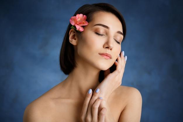 Chiuda sul ritratto di giovane donna tenera con il fiore rosa in capelli sopra la parete blu Foto Gratuite