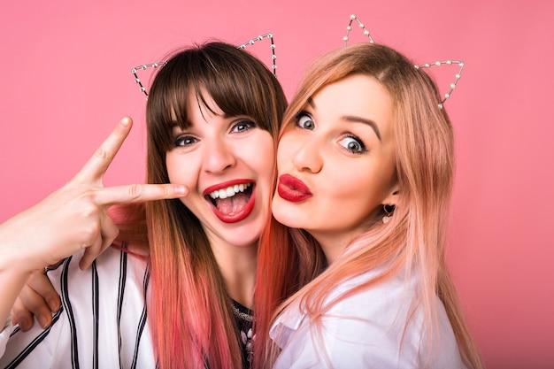 Close up ritratto di due felice uscito donna che indossa accessori per capelli cat party, trucco luminoso, divertenti emozioni pazze, amici che si godono la festa, muro rosa Foto Gratuite