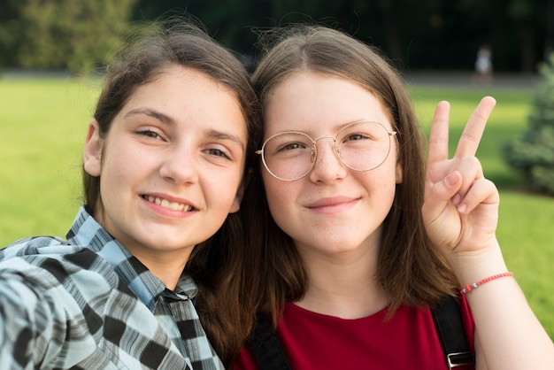 Close up portrait of two smiling school girls Free Photo