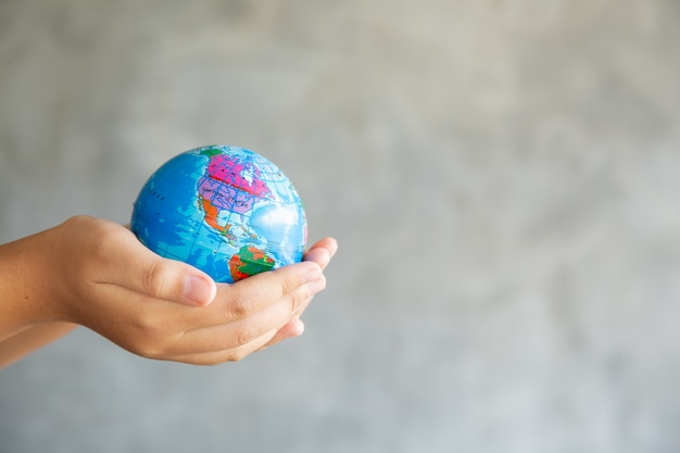 Close-up portrait of woman is holding global in her hands on gray Free Photo