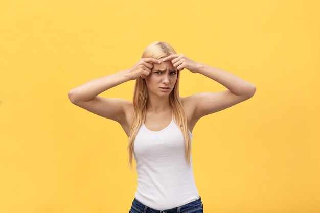 Close-up portrait of worried girl with acne problem, touching face, spa, therapy, treatment, isolated over yellow background Premium Photo