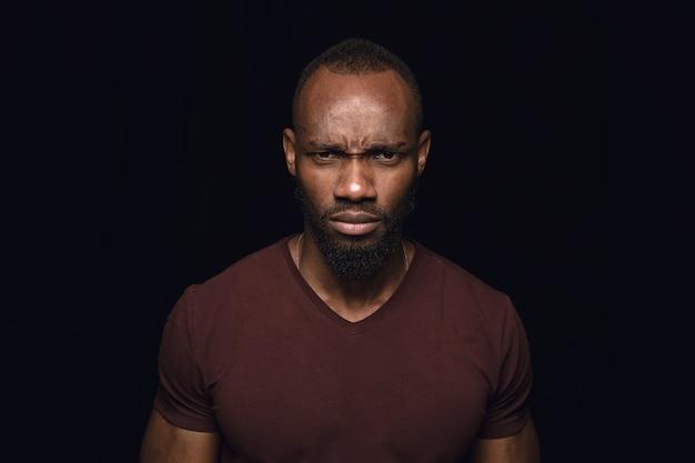 Close up ritratto di giovane uomo africano isolato sul nero Foto Gratuite