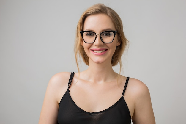 Ritratto del primo piano di giovane donna sexy attraente in occhiali alla moda, intelligente e fiducioso, sorridente e felice, vestito nero, stile elegante, modello in posa su sfondo bianco studio, isolato Foto Gratuite