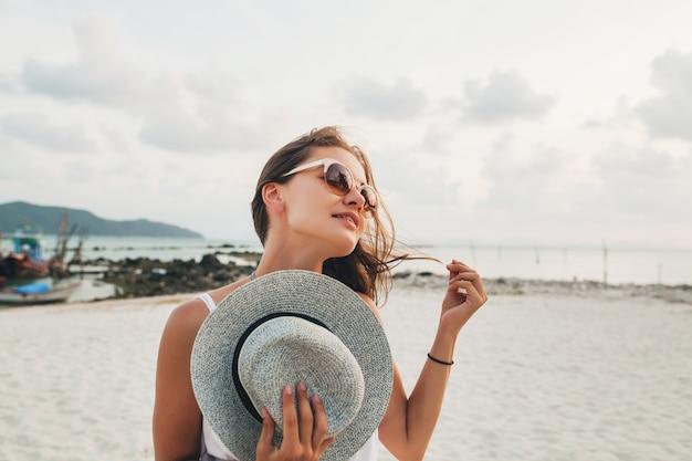 Close up ritratto di giovane donna sorridente attraente tenendo il cappello di paglia sulla spiaggia tropicale indossando occhiali da sole Foto Gratuite