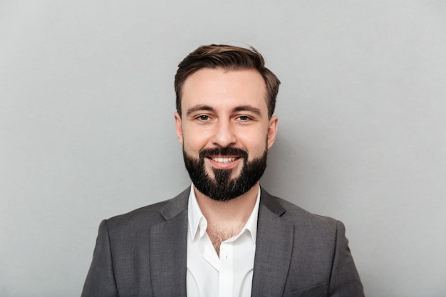 Close up portrait of young bearded man in white shirt and jacket posing on camera with broad smile, isolated over gray Free Photo