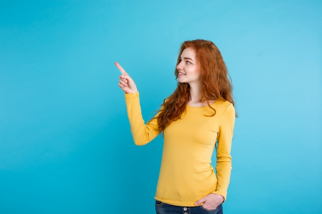 Close up portrait young beautiful attractive redhair girl happy with something and pointing finger. blue pastel background. copy space. Free Photo