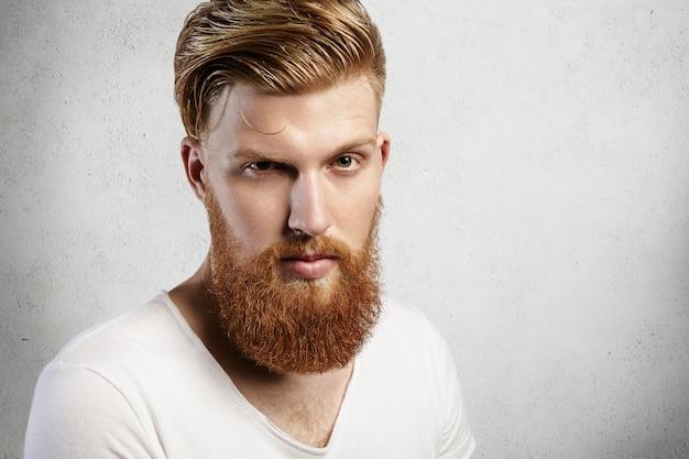 Ritratto del primo piano di giovane uomo caucasico con barba lunga allo zenzero e acconciatura alla moda. il giovane hipster dà uno sguardo indagatore con un sopracciglio alzato. la sua pelle è perfetta e l'espressione riservata. Foto Gratuite