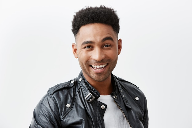 Close up portrait of young cheerful dark-skinned american man with curly hair in white t-shirt and leather jacket smiling brightly, looking in camera with happy and excited face expression. Free Photo
