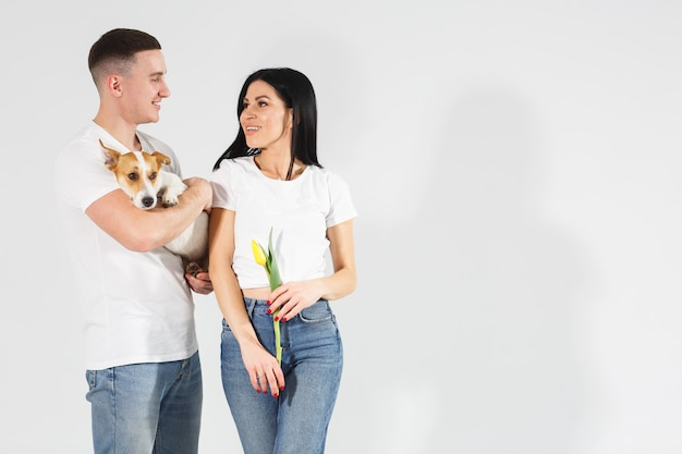 Close up portrait young couple with yellow flowers and dog . lovely couple embracing with dreamy amorous expression. happy dog life. lovely family. celebrating woman's day. Premium Photo