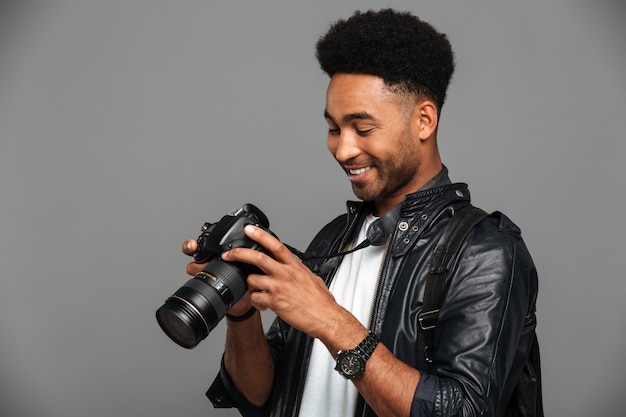Close-up portrait of young happy afro american man holding and looking at photo camera screen Free Photo