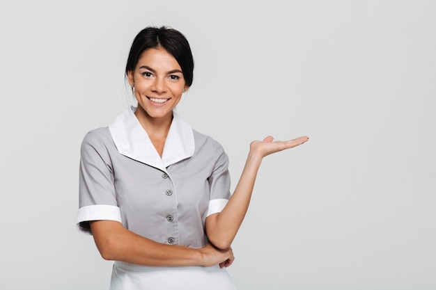 Close-up portrait of young happy housekeeper in uniform showing empty palm Free Photo