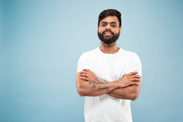 Close up portrait of young indian man in white shirt.  posing, standing and smiling, looks calm. Free Photo