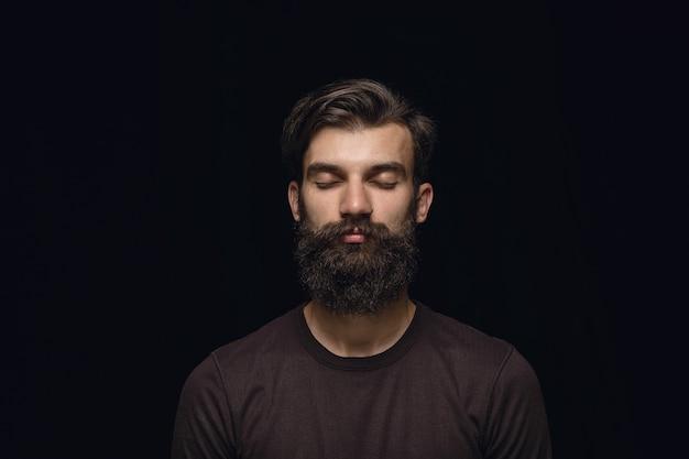 Close up ritratto di giovane uomo su nero studio Foto Gratuite
