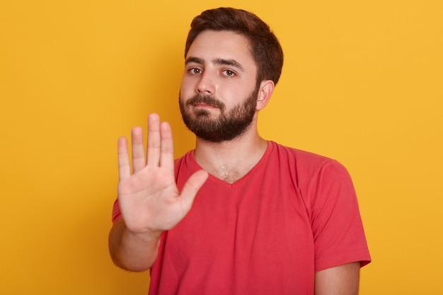 Chiuda sul ritratto del giovane che richiede l'arresto con la sua mano, il tipo bello che porta la maglietta rossa, mostrando il gesto di arresto Foto Gratuite