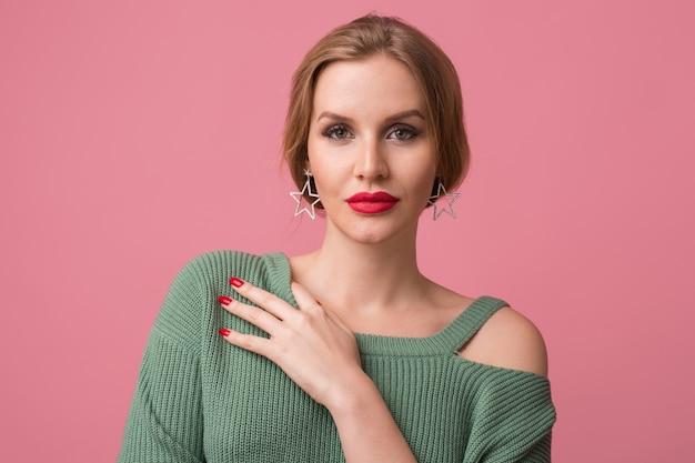 Ritratto del primo piano di giovane donna attraente sexy, trucco alla moda, labbra rosse, maglione verde, modello in posa in studio, isolato, sfondo rosa, orecchini, guardando a porte chiuse Foto Gratuite
