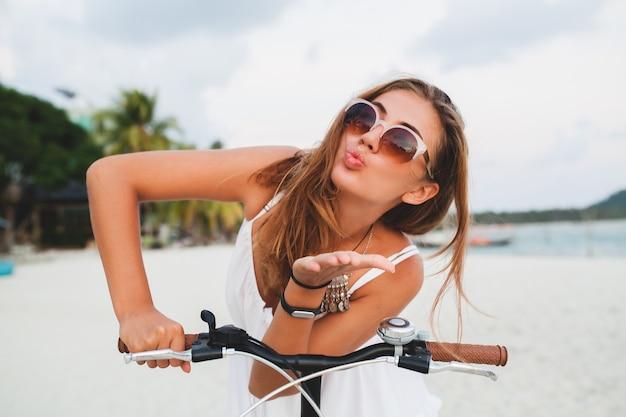 Chiuda sul ritratto di giovane donna sorridente in vestito bianco che guida sulla spiaggia tropicale sugli occhiali da sole della bicicletta che viaggiano sulle vacanze estive in tailandia Foto Gratuite