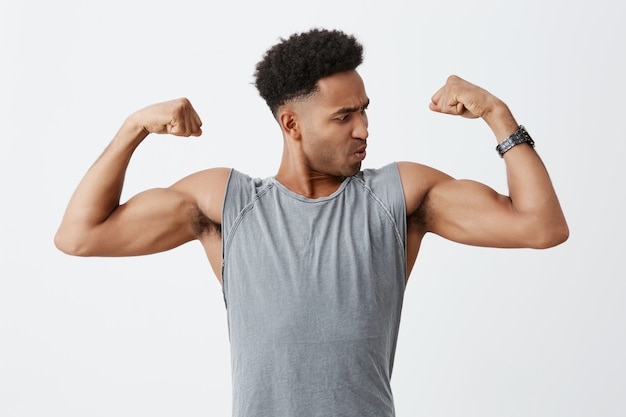 Close up portrait of young sporty dark-skinned man with afro hairstyle in grey shirt showing his muscles, looking at it with concentrated face expression. health and beauty Free Photo