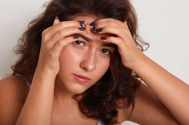 Close up portrait of young woman squeezing pimple on her forehead while standing over white studio, attractive dark haired female having problems with facial skin. skincare concept. Premium Photo