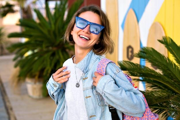 Закройте вверх позитивный портрет стильной хипстерской женщины, позирующей перед местом для серфинга, молодежной модной одеждой, синими солнцезащитными очками, джинсовой курткой и рюкзаком, пальмами вокруг. Бесплатные Фотографии