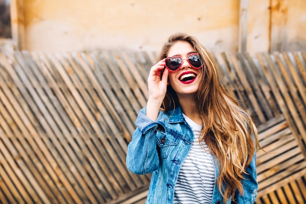 Close-up posrtait of magnificent female model in retro denim jacket, holding sunglasses and lookin up. sensual young woman with beautiful long hair posing gladly in front of the unusual wooden fence. Free Photo