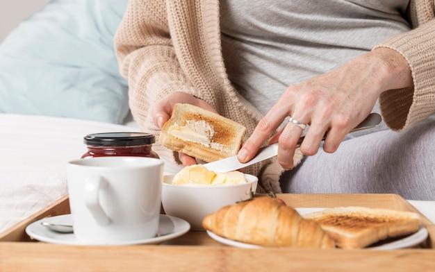Крупным планом беременная женщина ест бранч в постели Бесплатные Фотографии