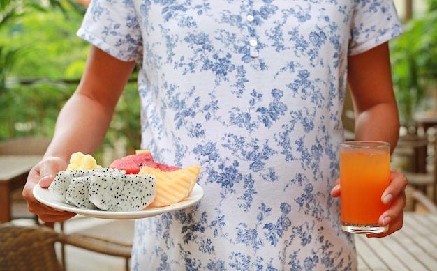 Close-up pregnant woman holding fruits in plate and glass of orange juice Premium Photo