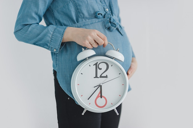 Close-up of pregnant woman showing clock Premium Photo