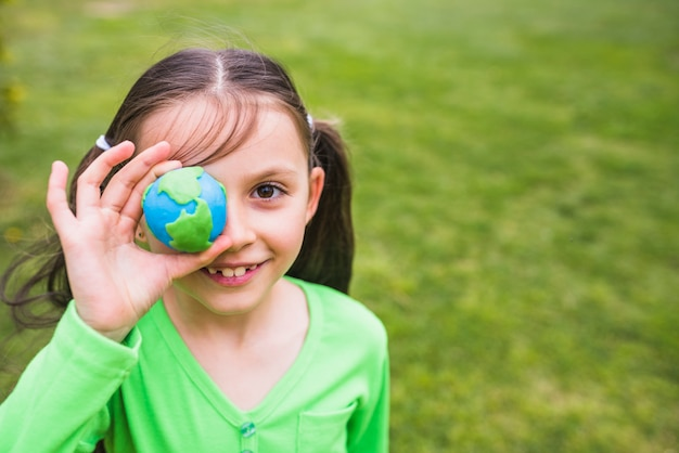 Close-up of a pretty girl holding clay globe in hand Free Photo