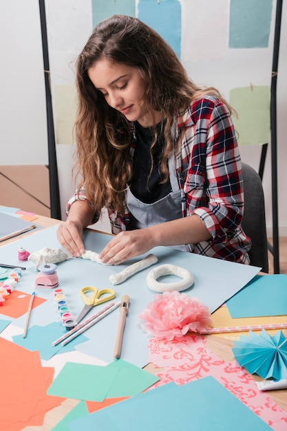 Close-up of pretty woman making craft using white clay Free Photo
